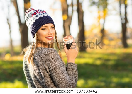Beautiful young blonde Caucasian woman in park, holding a takeaway cup of coffee, smiling, posing, wearing modern knitted beanie hat. Medium retouch, vibrant colors, natural light.