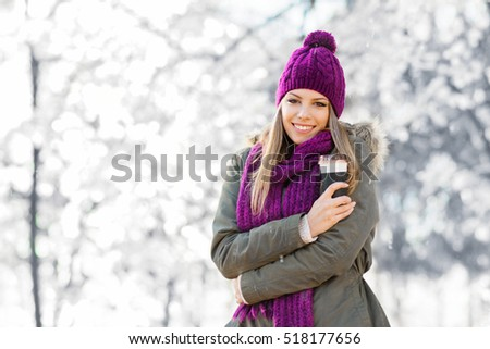 Beautiful young blonde Caucasian woman in winter jacket, knitted beanie hat and scarf, holding a takeaway cup of coffee or tea, outdoors in park on snowing winter day. Natural lighting, retouched.