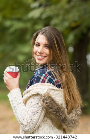 Beautiful young blonde Caucasian woman smiling wearing fashionable autumn outfit. Cute teenage girl in beige sweater and plaid shirt holding takeaway coffee cup in fall in park. Vertical, retouched. - stock photo
