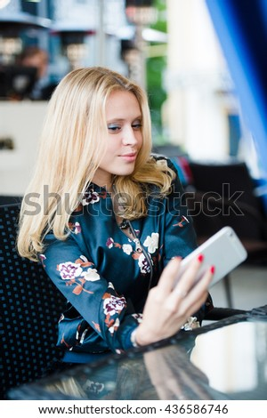 Beautiful young blonde Caucasian woman taking a selfie with smartphone outdoors - stock photo