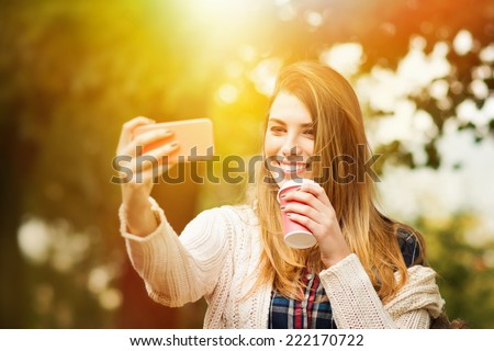 Beautiful young blonde Caucasian woman with takeaway coffee taking a selfie with smartphone outdoors in park in autumn. - stock photo