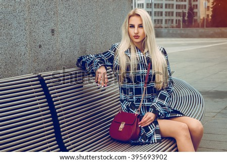 Beautiful young blonde fashion model posing outdoors and looking at the camera. fashion model posing outdoors. fashionable and glamour concept. - stock photo