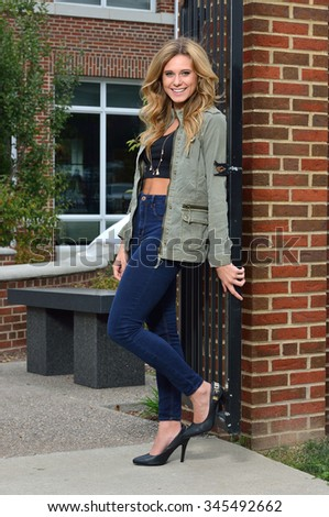 Beautiful young blonde female student on campus - fashion, green jacket and jeans leaning against gate - stock photo
