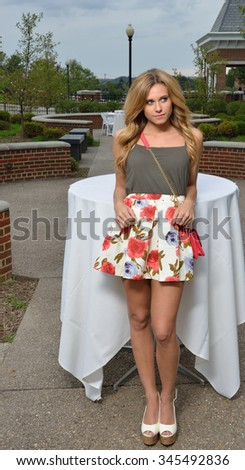 Beautiful young blonde female student on campus - in courtyard with tables waiting for dinner - stock photo