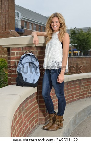 Beautiful young blonde female student on campus - standing next to backpack - stock photo