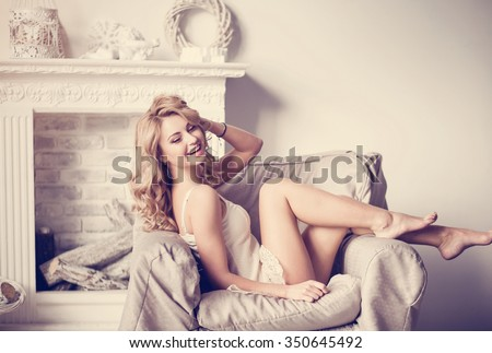 Beautiful young blonde girl in a tender erotic underwear sitting in a chair near the fireplace in a large, bright bedroom with elements Christmas decoration - stock photo