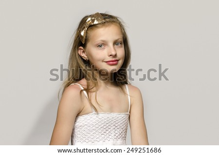 Beautiful young blonde girl in white dress smiling, portrait of an adorable kid - stock photo