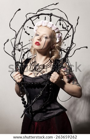 beautiful young blonde girl with black tears in Gothic black corset and red skirt with artificial white roses in her hair - stock photo
