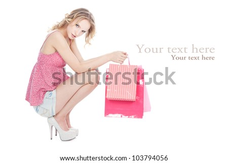 Beautiful young blonde girl with pink shopping bags over white - stock photo