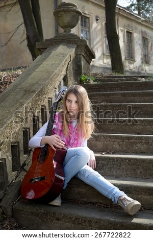 Beautiful Young Blonde Hair Model with Guitar Sitting on the Staircase in the Park on Sunny Spring Day - stock photo
