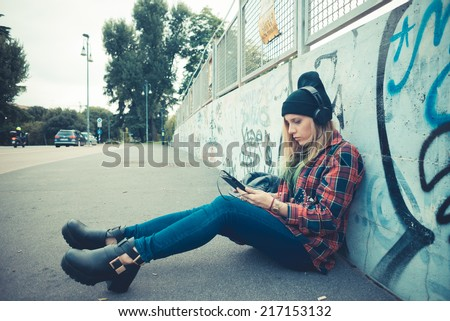 beautiful young blonde hair woman hipster listening music in the city - stock photo