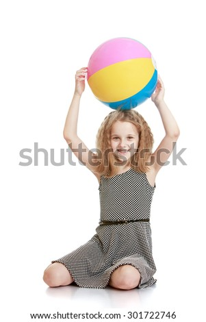 Beautiful young blonde haired girl sitting on the floor. The girl dressed in a gray silk dress , in the hands over the head she is holding a large inflatable striped ball. The girl is vacationing with - stock photo