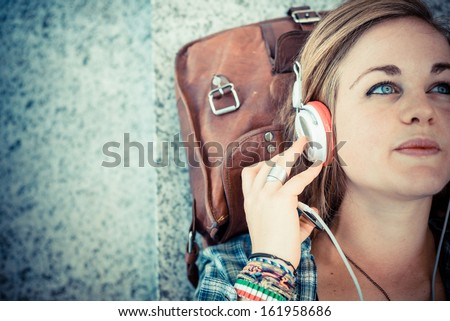 beautiful young blonde hipster woman listening music in urban landscape - stock photo