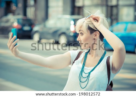 beautiful young blonde short hair hipster woman selfie in the city - stock photo
