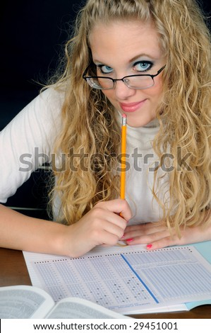 Beautiful young blonde student holding pencil to chin - stock photo