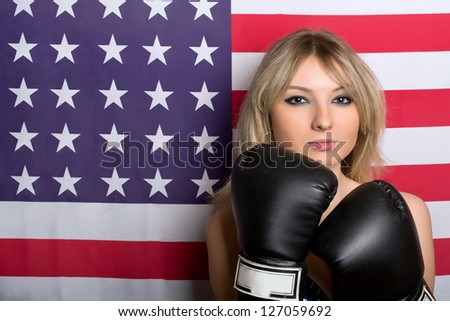 Beautiful young blonde with boxing gloves on a background of the American flag