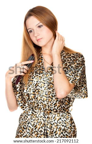 Beautiful young blonde with comb on white background