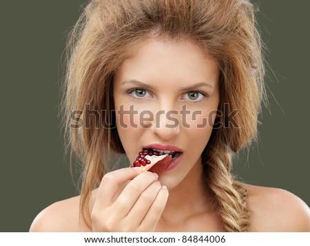 beautiful young blonde woman biting a pomegranate - stock photo