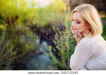 beautiful young blonde woman in a spring park.  - stock photo