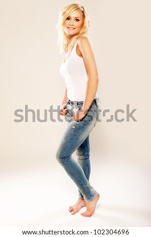 Beautiful young blonde woman in jeans posing barefoot with her thumbs hooked in her pockets