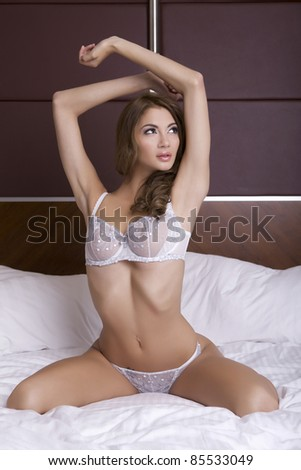 Beautiful young blonde woman in lingerie lying on the bed - stock photo