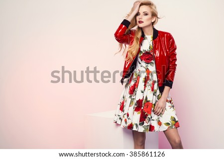 beautiful young blonde woman in nice spring dress and red plactic jacket posing in a studio. Fashion photo - stock photo