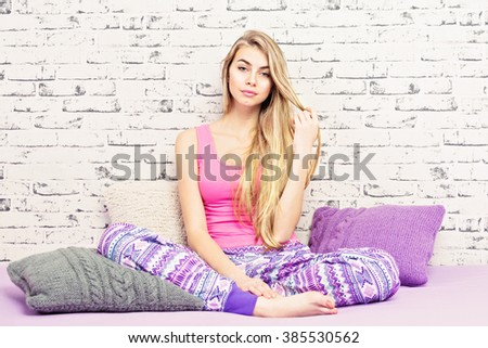 Beautiful young blonde woman in pink and purple pajamas, in bed with modern knitted pillows, against white brick wall. Gorgeous teenage girl with blonde long straight hair relaxing at home in bedroom. - stock photo