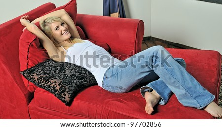 Beautiful young blonde woman lounging on red chaise lounge (chaise longue) chair in white tank top and blue jeans - stock photo