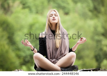 Beautiful young blonde woman meditating outdoors.Yoga woman on green grass.Calm woman meditating sitting in a park with closed eyes.Sport, meditation, park and lifestyle concept-woman meditating - stock photo