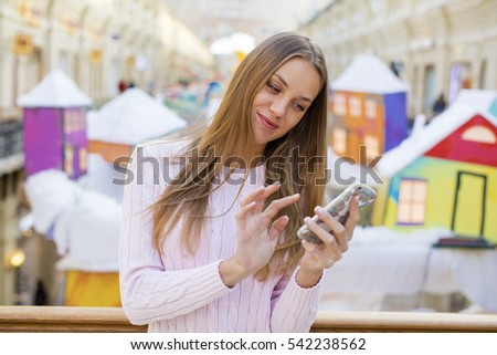Beautiful young blonde woman reading a message on the phone, indoor shop