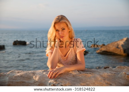 Beautiful young blonde woman resting on a beach at dusk in summer - sea side sunset - stock photo