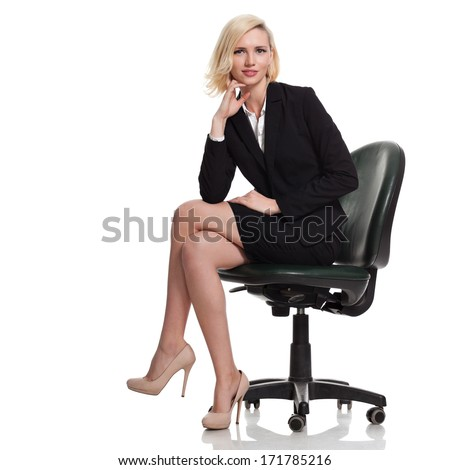 beautiful young blonde woman sitting on a chair and smiling; holding her hand under her chin - stock photo