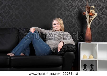 Beautiful young blonde woman sitting on black leather sofa at home, wearing grey knitted sweater, blue jeans and just relaxing.