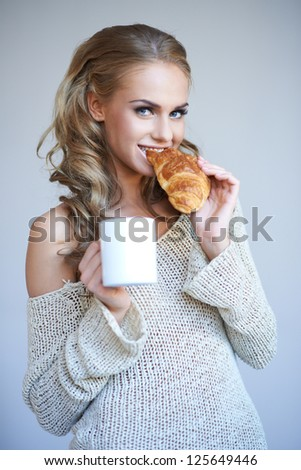 Beautiful young blonde woman standing enjoying a fresh crispy croissant and a mug of coffee for her breakfast