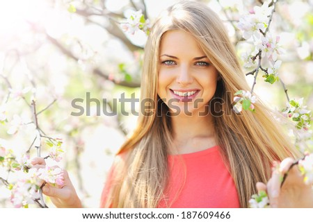 Beautiful young blonde woman standing near blooming tree - stock photo