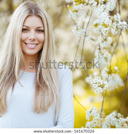Beautiful young blonde woman standing near the apple tree - stock photo