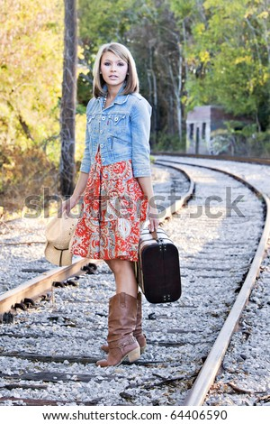 Beautiful young blonde woman walking on railroad tracks with suitcase and cowboy hat - stock photo