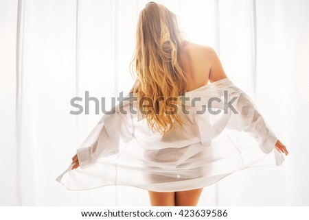 Beautiful young blonde woman wearing a white mens shirt next to a bright sun-lit window covered by a sheer white curtain - stock photo