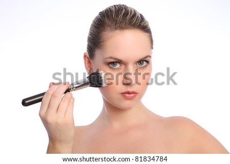 Beautiful young blonde woman with bright blue eyes using stippling make up brush also referred to as a cosmetics powder brush.