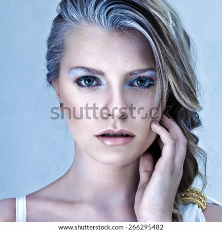 Beautiful young blonde woman with fantasy frost make-up studio shot - stock photo
