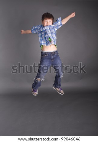 Beautiful young boy jumping in the air on a grey background