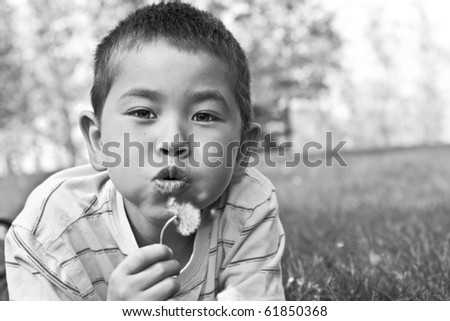 Beautiful young boy with bright eyes blowing a dandelion in black and white
