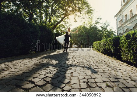 Beautiful young bride and handsome groom holding in the air outdoors near old mansion at sunset shadow - stock photo