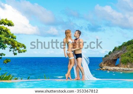 Beautiful young bride in a white bikini, veil and garter on her leg and groom on the edge of the infinity-edge pool. Tropical sea in the background. - stock photo
