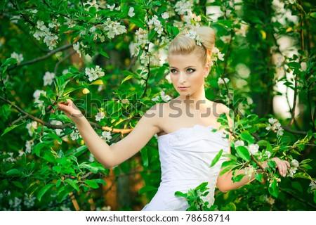 beautiful young bride in garden - stock photo