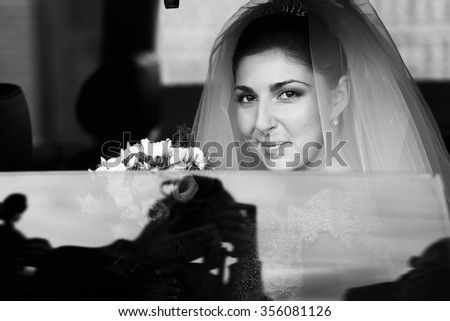 Beautiful young bride in the car with bouquet of flowers on the wedding day