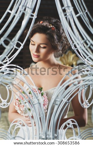 Beautiful young bride in wedding gown with bouquet. Interior shot. - stock photo