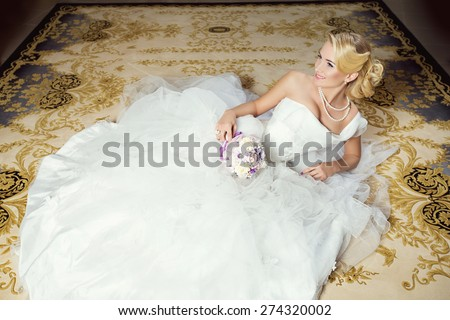 Beautiful young bride in white fluffy dress lying on carpet - stock photo