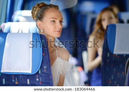 Beautiful young bride portrait in a wedding bus - stock photo