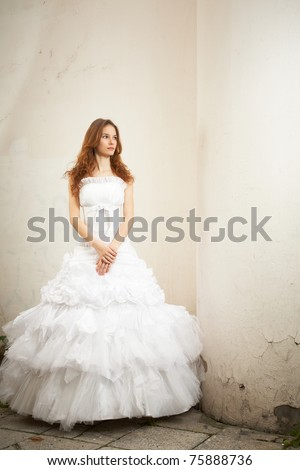 Beautiful young bride posing next to the old column - stock photo